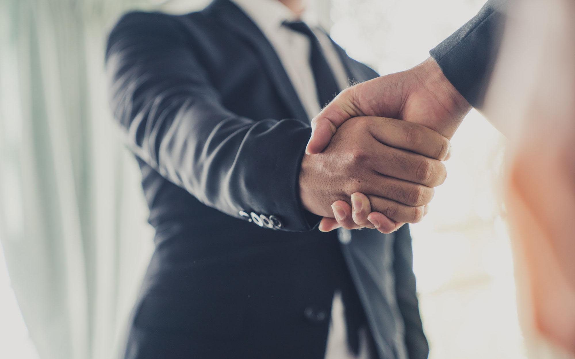man in suit shaking hands